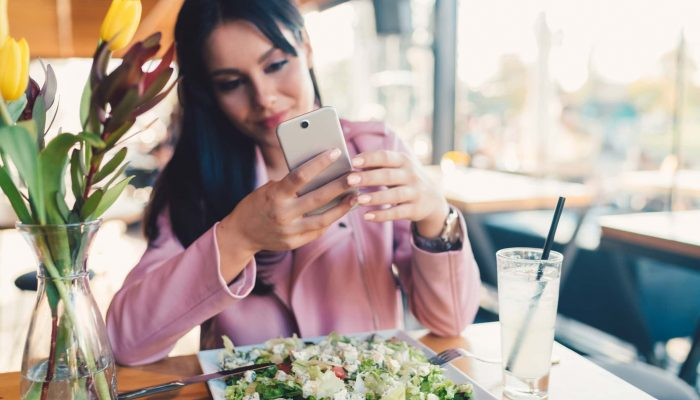 Woman in cafe using smartphone to make photos