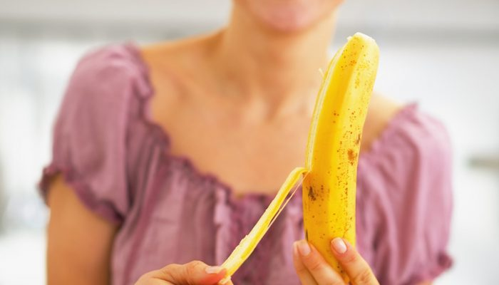 Closeup on young woman peeling banana; Shutterstock ID 174307997; PO: today.com