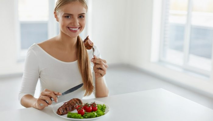 Woman Eating Food. Beautiful Smiling Female Eating Delicious Grilled Meat With Fresh Organic Vegetables In Kitchen. Healthy Attractive Girl Dinning Having Beef Steak With Tomatoes And Salad. Nutrition