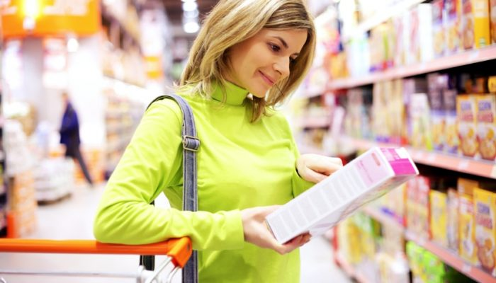 Young woman checking food labeling in supermarket