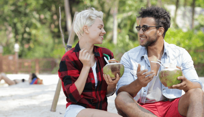 videoblocks-couple-on-beach-drink-coconut-cocktail-talking-sit-under-palm-trees-happy-man-and-woman-tourists-communication-slow-motion-60_h12gfd2ce_thumbnail-full01 (1)
