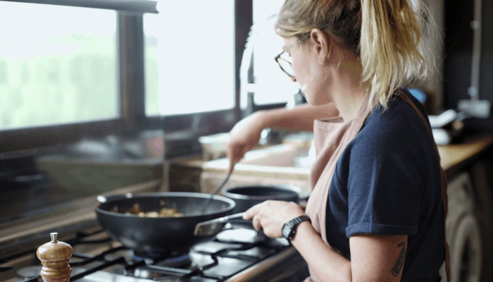 videoblocks-young-pretty-female-chef-wearing-a-red-apron-prepares-fresh-steaming-dish-in-a-deep-fry-wok-pan-on-big-industrial-kitchen-stove-in-design-loft_rhhthohxz_thumbnail-full01