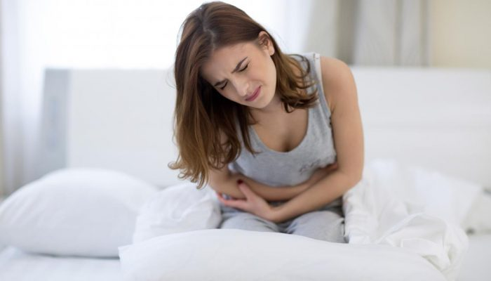 woman-clutching-stomach-in-pain-because-of-ibs
