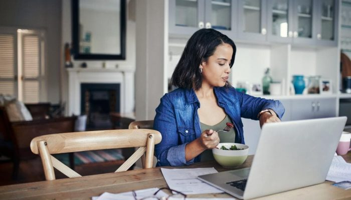 woman-eating-food-at-table-in-front-of-laptop-looking-at-her-watch